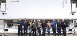 Schrag Hamburg. Pracownicy stojący przed maszyną do produkcji profili Z, profili C, kształtowników zimnogiętych, obróbek blacharskich, elewacji.